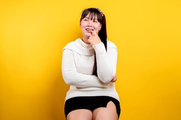 Porträt einer schönen asiatischen frau mit einem lächelnden gesicht. asiatische frau, die freizeitkleidung trägt. thailändischer lebensstil. süßes mädchen strahlendes lächeln auf gelbem hintergrund