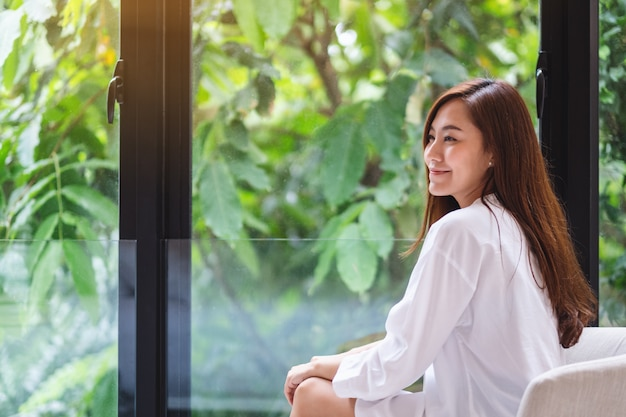 Porträt einer schönen asiatischen frau mit grüner natur außerhalb des fensters