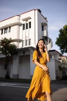 Porträt einer schönen asiatischen frau mit smartphone im freien in der stadt