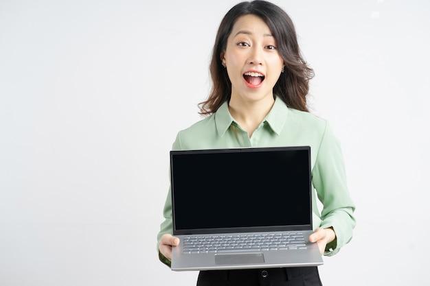 Porträt einer schönen asiatischen geschäftsfrau, die ihren laptop mit einem leeren bildschirm hält