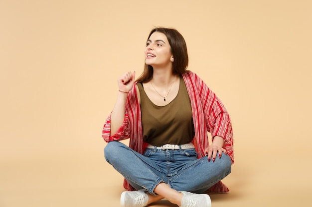 Porträt einer schönen attraktiven jungen frau in freizeitkleidung, die beiseite sitzt, isoliert auf pastellbeigem wandhintergrund im studio. menschen aufrichtige emotionen, lifestyle-konzept. kopieren sie platz.