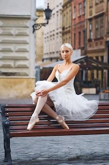 Porträt einer schönen balletttänzerin, die auf der bank im stadtzentrum ruht und anmutig städtisches modekonzept der schönheitseleganz sitzt.