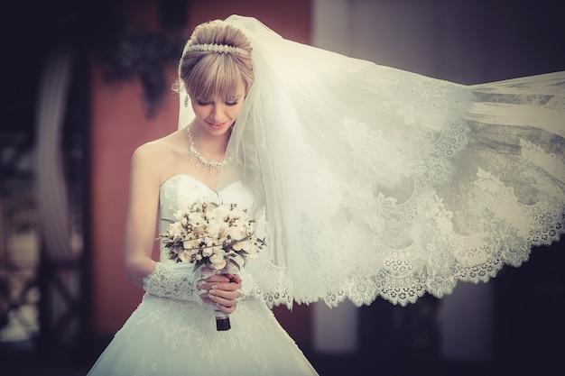Porträt einer schönen blonden braut mit hochzeitsblumenstrauß in den händen