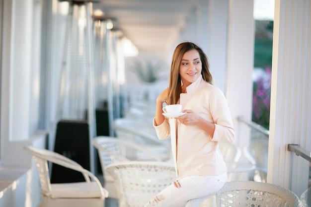 Porträt einer schönen blonden frau, die in einer weißen bluse sitzt bei tisch gekleidet wird, trinkt kaffee am terrassencafé.