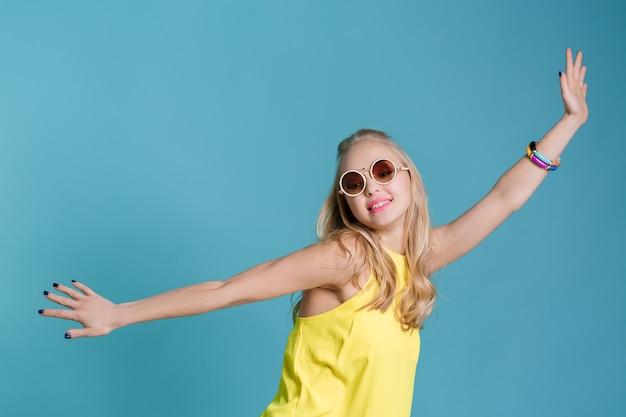 Porträt einer schönen blonden frau mit sonnenbrille und gelbem hemd, die auf blauem hintergrund sorglos tanzt...
