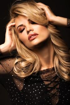 Porträt einer schönen blondine auf einem schwarzen
