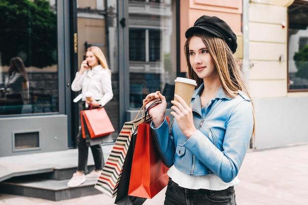 Porträt einer schönen blondine, die lächelt und kaffee in der einen hand und einkaufstaschen in der anderen hält