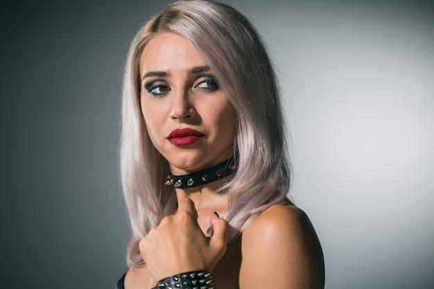 Porträt einer schönen blondine mit roten lippen auf dunklem hintergrund in einem kragen mit spikes
