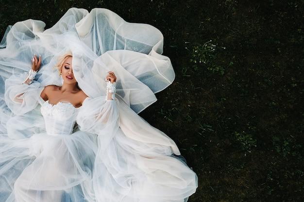 Porträt einer schönen braut, die auf dem boden in einem weißen hochzeitskleid liegt. foto einer eleganten braut auf dem grünen gras. oberes foto der braut.