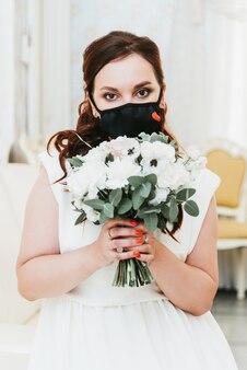 Porträt einer schönen braut mit einem blumenstrauß in einer medizinischen schutzmaske auf ihrem gesicht. hochzeit während der pandemie covid-19.