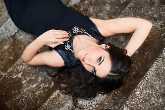 Porträt einer schönen brunettefrau in einem eleganten schwarzen kleid