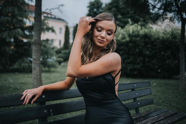 Porträt einer schönen eleganten frau in einem schicken schwarzen kleid, die auf einer bank im park sitzt