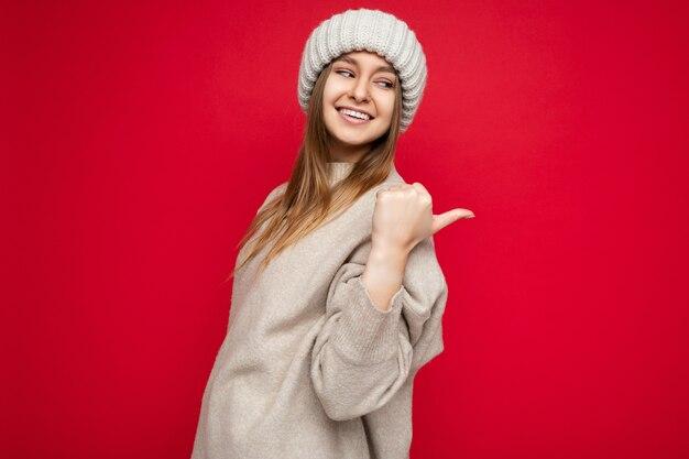 Porträt einer schönen emotionalen, positiv lächelnden, glücklichen promoterin, die auf die seite der kopie zeigt