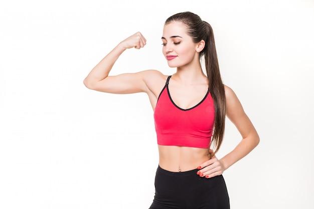 Porträt einer schönen fitnessfrau, die ihren bizeps auf einer weißen wand zeigt