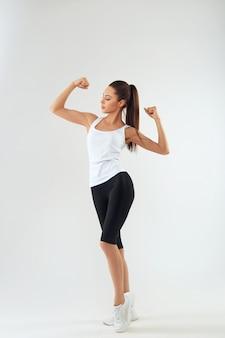 Porträt einer schönen fitnessfrau, die ihren bizeps lokalisiert auf einer weißen wand zeigt