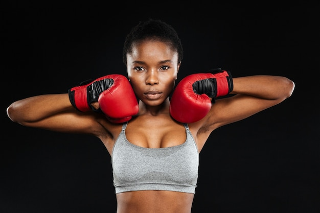 Porträt einer schönen fitnessfrau, die in boxhandschuhen steht, isoliert auf einer schwarzen wand