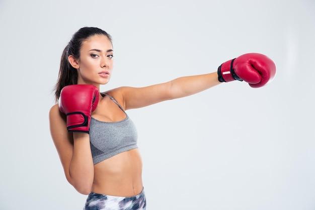 Porträt einer schönen fitnessfrau in den boxhandschuhen lokalisiert auf einer weißen wand