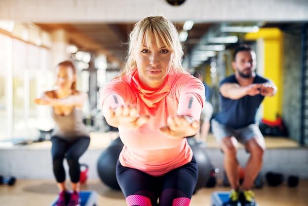 Porträt einer schönen fokussierten sportlehrerin, die einige kniebeugen mit ausgestreckten händen vor sich macht.