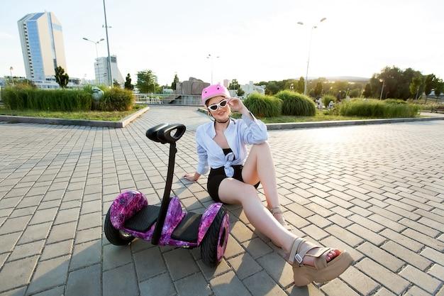 Porträt einer schönen frau auf einem hoverboard oder kreiselroller im park