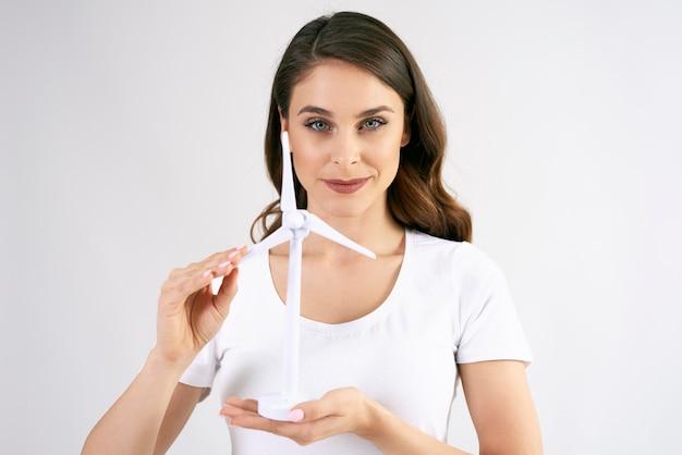 Porträt einer schönen frau, die ein modell einer windkraftanlage hält