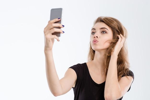 Porträt einer schönen frau, die ein selfie-foto auf dem smartphone macht, isoliert auf weißem hintergrund