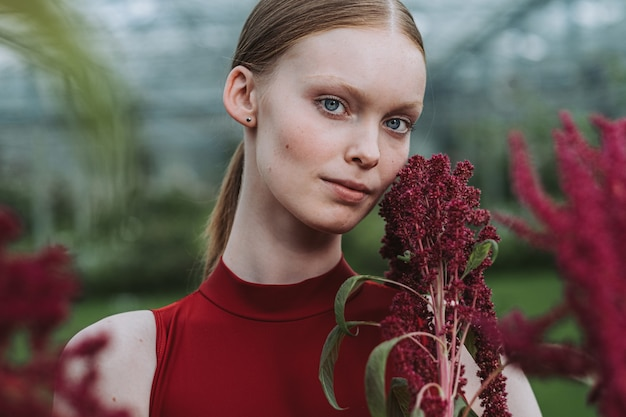 Porträt einer schönen frau, die eine amaranthpflanze hält