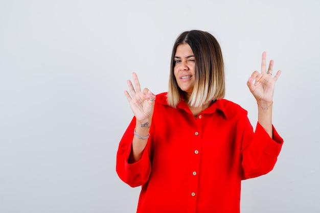 Porträt einer schönen frau, die eine gute geste zeigt, während sie in roter bluse blinkt und selbstbewusste vorderansicht sieht
