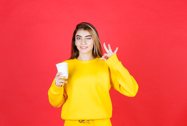 Porträt einer schönen frau, die eine plastiktasse tee hält und ein ok-zeichen gibt