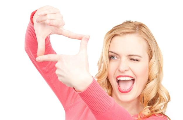 Porträt einer schönen frau, die einen rahmen mit den fingern erstellt