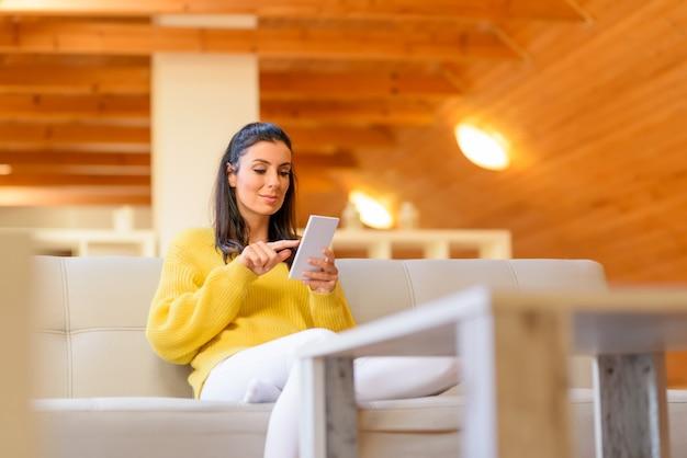 Porträt einer schönen frau, die ihr smartphone im wohnzimmer benutzt