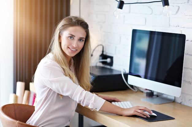 Porträt einer schönen frau, die im modernen home office arbeitet