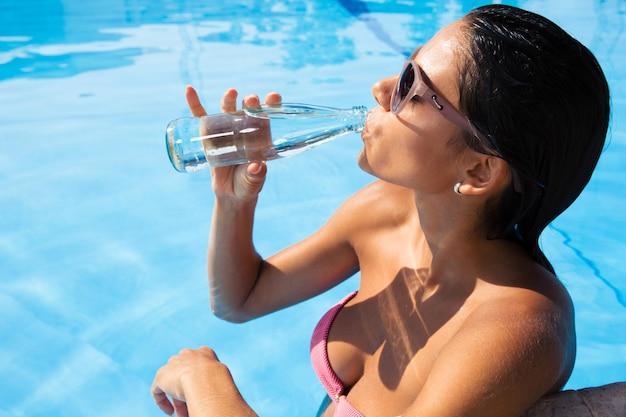 Porträt einer schönen frau, die im schwimmbad steht und draußen wasser trinkt