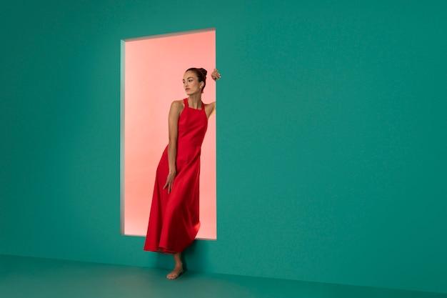 Porträt einer schönen frau, die in einem fließenden roten kleid mit kopienraum posiert