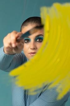 Porträt einer schönen frau, die in einem rollkragenpullover mit gelbem pinselstrich posiert