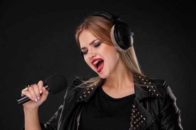 Porträt einer schönen frau, die in mikrofon mit kopfhörern im studio auf schwarz singt