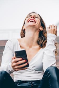 Porträt einer schönen frau, die lächelt und ihr telefon betrachtet