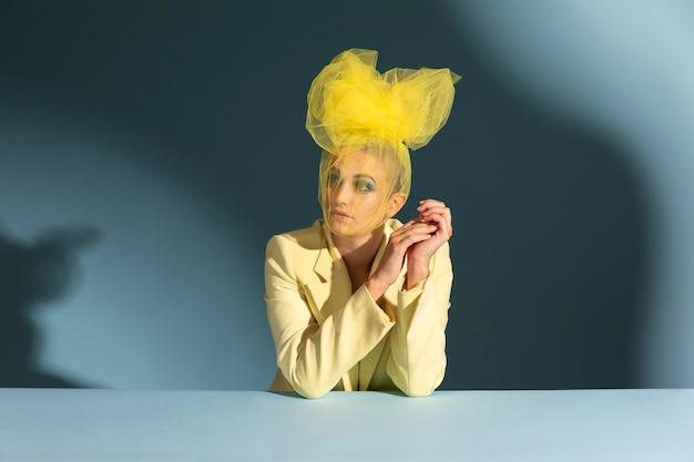 Porträt einer schönen frau, die mit einem avantgardistischen kopfstück posiert