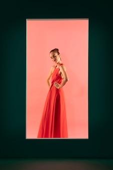 Porträt einer schönen frau, die mit einem fließenden roten kleid posiert