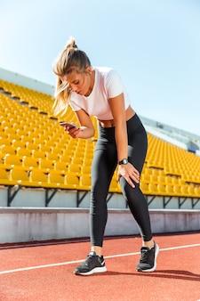 Porträt einer schönen frau, die nach dem laufen ruht und smartphone auf freiluftstadion verwendet