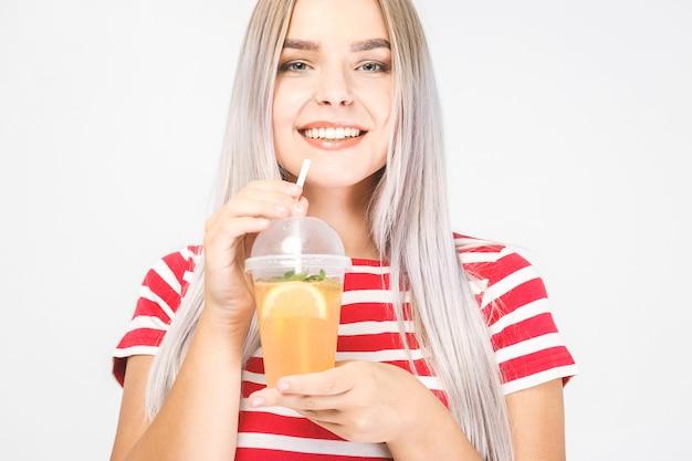 Porträt einer schönen frau, die orangensaftglas hält. lächelndes mädchen isolierte porträt über weiß. freizeitkleidung.