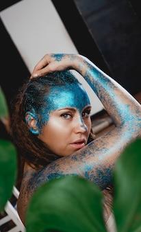 Porträt einer schönen frau, die wie im wilden wald aufwirft. frau mit blauen glitzern auf ihrem gesicht. menschen sind anders als andere. individualität