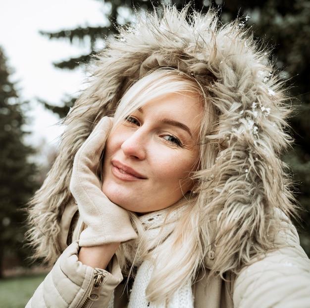 Porträt einer schönen frau, die winterjacke mit kapuze trägt
