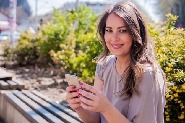 Porträt einer schönen frau eingabe auf dem smartphone in einem park mit einem grünen unfocused hintergrund. fröhliche frau sms mit ihrem smartphone in einem park