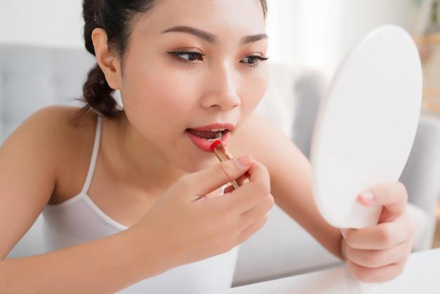 Porträt einer schönen frau, färbt ihre lippen lippenstift rosa und schaut in den spiegel