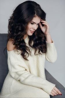 Porträt einer schönen frau. frau im winterpullover und schönes lockiges haar.