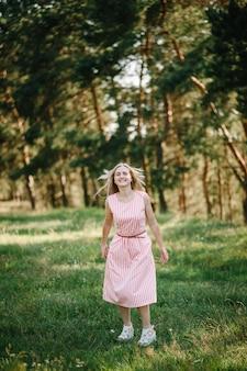 Porträt einer schönen frau im grünen gras auf dem feld weggelaufen, natur im sommerurlaub. das spielen im park zur sonnenuntergangszeit. nahaufnahme.