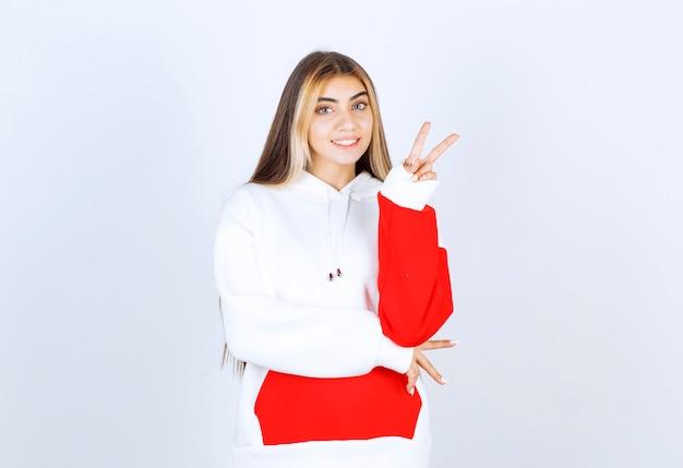 Porträt einer schönen frau im hoodie, die steht und victory-zeichen zeigt