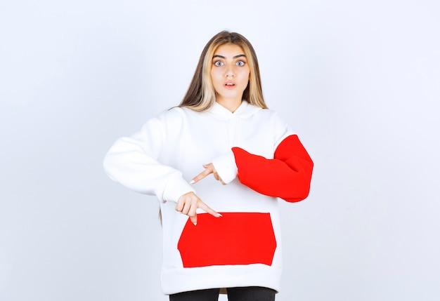 Porträt einer schönen frau im warmen hoodie, die auf das handgelenk steht und zeigt