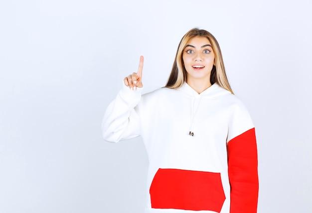 Porträt einer schönen frau im warmen hoodie, die nach oben steht und zeigt