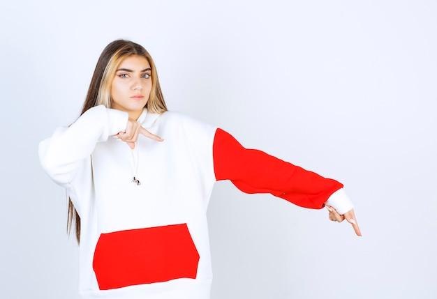 Porträt einer schönen frau im warmen hoodie, die nach unten steht und zeigt